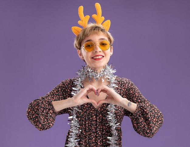 Jovem bonita sorridente usando bandana de chifres de rena e guirlanda de ouropel em volta do pescoço com óculos fazendo um sinal de coração isolado na parede roxa