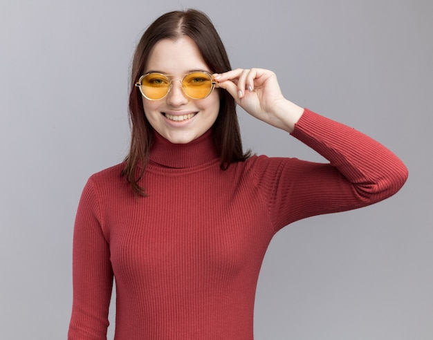 Jovem bonita sorridente usando e agarrando óculos de sol