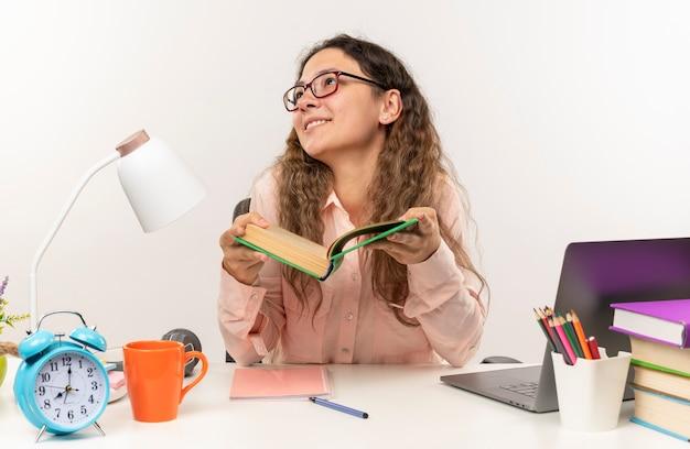 Jovem bonita sorridente usando óculos, sentada na mesa com as ferramentas da escola, fazendo sua lição de casa segurando o livro, olhando para cima isolado na parede branca