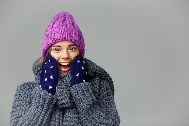 Jovem bonita surpreendeu a mulher de cabelos louro na camisola knited chapéu e luvas sorrindo em cinza.