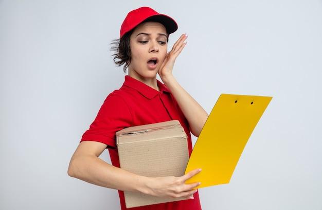 Jovem bonita, surpresa, entregadora, segurando uma caixa de papelão e olhando para a prancheta