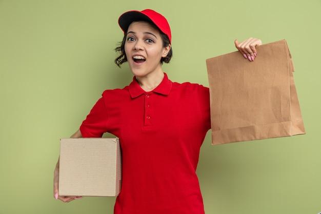 Jovem bonita surpresa, entregadora, segurando uma embalagem de papel para comida e uma caixa de papelão