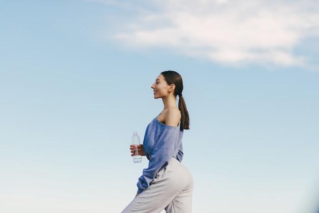 Jovem bonita treinando com garrafa de água