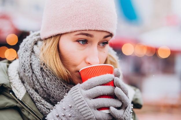 Jovem bonita usando chapéu e suéter rosa bebendo chocolate quente