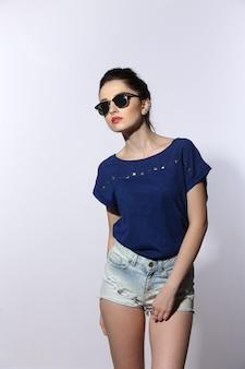 Jovem bonita vestindo jeans e óculos de sol