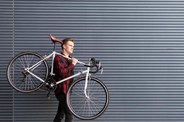 Jovem bonitão carrega uma bicicleta quebrada nos ombros contra a parede