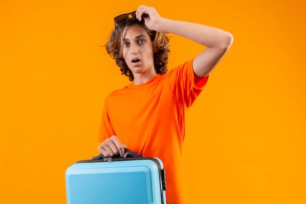 Jovem bonitão de camiseta laranja segurando a mala de viagem, adiando os óculos, olhando surpreso e espantado em pé