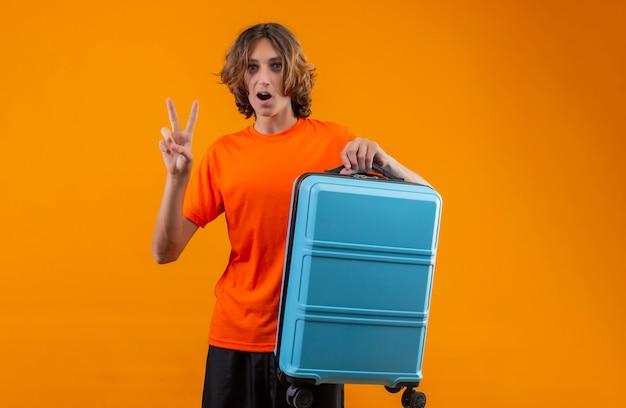 Jovem bonitão de camiseta laranja, segurando a mala de viagem, mostrando o número dois ou sinal de vitória, olhando surpreso em pé