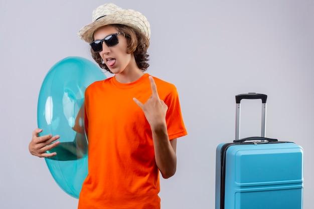 Jovem bonitão de camiseta laranja, usando óculos escuros pretos, segurando o anel inflável, feliz e positivo, fazendo o símbolo do rock em pé com mala de viagem