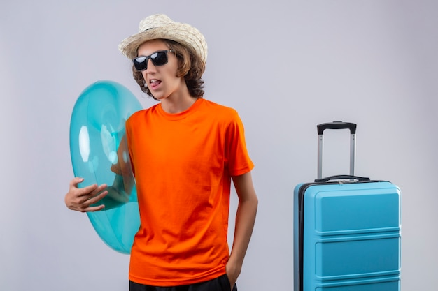 Jovem bonitão de camiseta laranja, usando óculos escuros pretos, segurando o anel inflável feliz e positivo saindo da língua em pé com mala de viagem