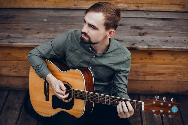 Jovem bonitão toca guitarra, pega um acorde, músico de rua