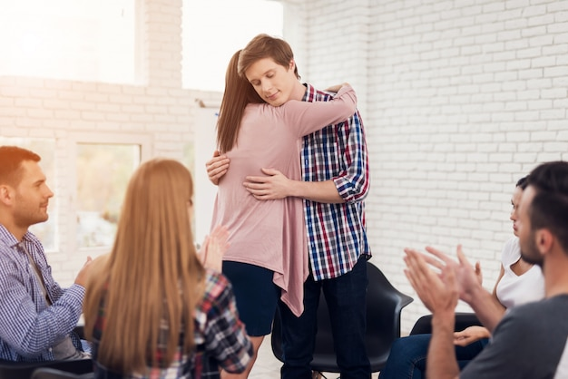 Jovem bonito abraça garota na reunião.