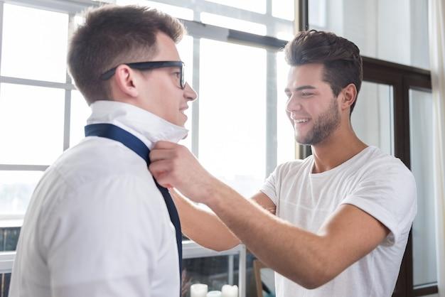 Jovem bonito amarrando a gravata do namorado enquanto passam algum tempo juntos e aproveitando o dia.