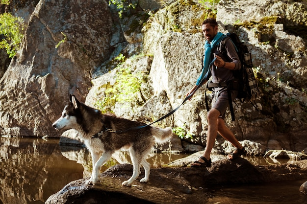 Jovem bonito andando com cães huskies no canyon perto da água