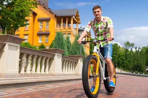 Jovem bonito andando de bicicleta amarela em frente a uma casa pintada de amarelo em uma estrada pavimentada de tijolos, vista de baixo ângulo