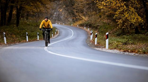 Jovem bonito andando de bicicleta em uma estrada rural pela floresta de outono