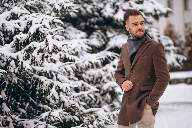 Jovem bonito andando em uma floresta de inverno