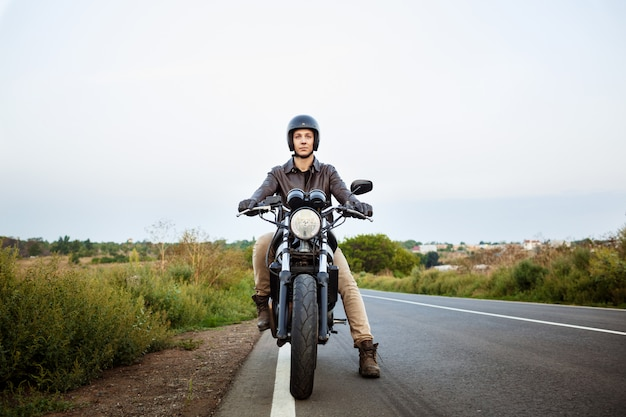Jovem bonito andar de moto na estrada rural.