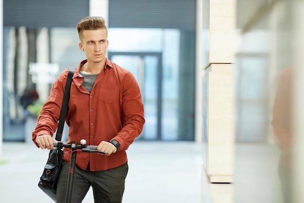 Jovem bonito andar de scooter na rua da cidade