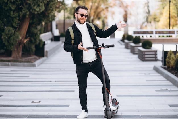 Jovem bonito, andar de scooter no parque