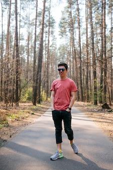 Jovem bonito ao ar livre no parque, caminhando no parque