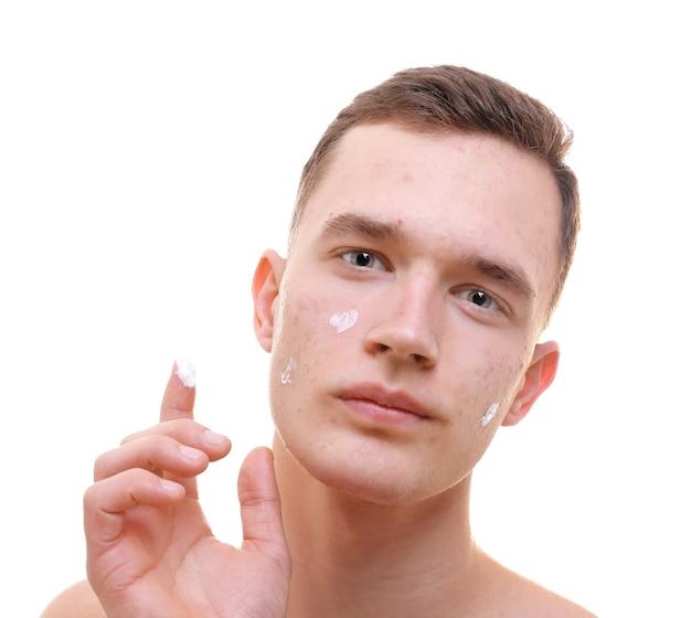 Jovem bonito aplicando creme para pele com problema no rosto, em fundo branco