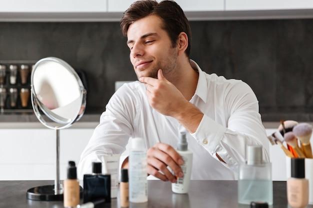 Jovem bonito aplicar produtos de maquiagem e beleza