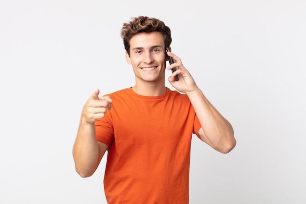 Jovem bonito apontando para a câmera, escolhendo você e falando com um telefone inteligente