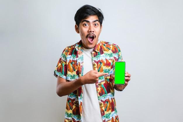 Jovem bonito asiático mostrando tela verde de smartphone sobre fundo branco isolado muito feliz apontando com a mão e o dedo para o lado
