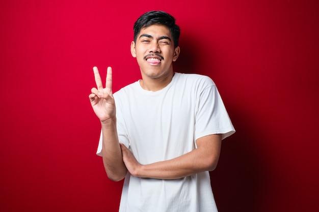 Jovem bonito asiático vestindo camiseta branca em pé sobre um fundo vermelho fazendo o símbolo da paz com os dedos no rosto, sorrindo, alegre, mostrando a vitória