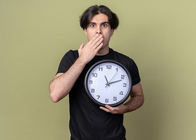 Jovem bonito assustado vestindo uma camiseta preta segurando um relógio de parede e a boca coberta com a mão isolada na parede verde oliva