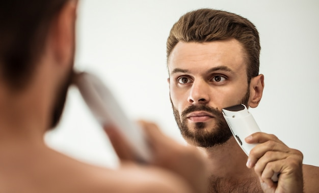 Jovem bonito barbear a barba no banheiro. retrato de um homem barbudo nu elegante, examinando seu espelho em casa de rosto.