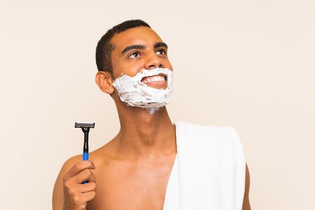 Jovem bonito barbear a barba, olhando para cima enquanto sorrindo