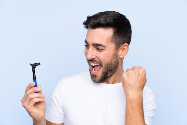 Jovem bonito barbear a barba sobre parede isolada comemorando uma vitória
