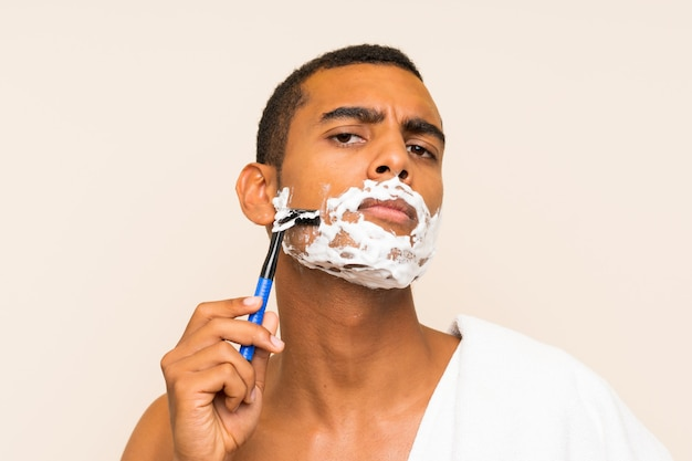 Jovem bonito barbear a barba sobre parede isolada