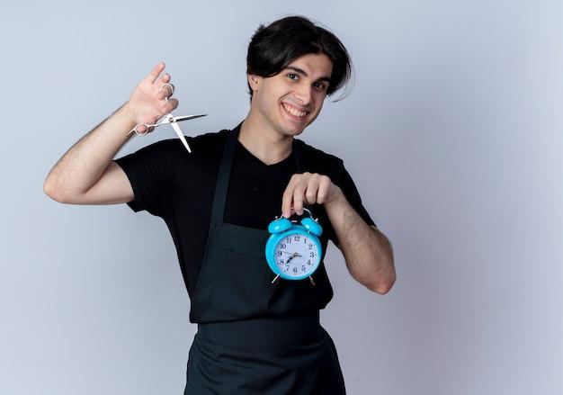 Jovem bonito barbeiro de uniforme sorridente segurando um despertador e uma tesoura isoladas em branco