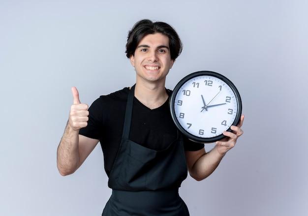 Jovem bonito barbeiro de uniforme sorridente segurando um relógio de parede com o polegar isolado no branco