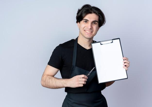 Jovem bonito barbeiro de uniforme sorridente segurando uma prancheta com uma tesoura isolada no branco