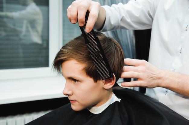 Jovem bonito barbeiro fazer corte de cabelo de menino bonitinho na barbearia.