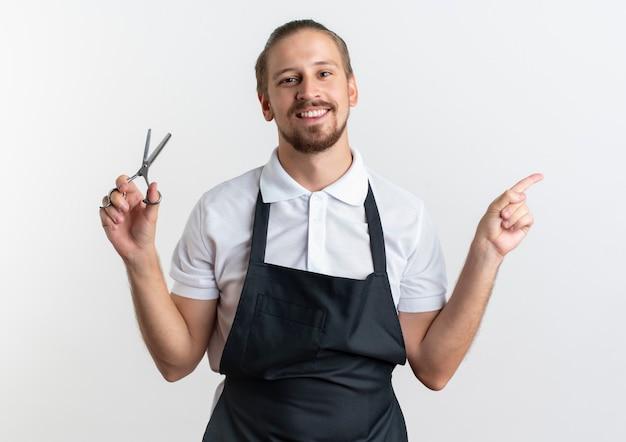 Jovem bonito barbeiro sorridente, usando uniforme, segurando uma tesoura e apontando para o lado isolado na parede branca