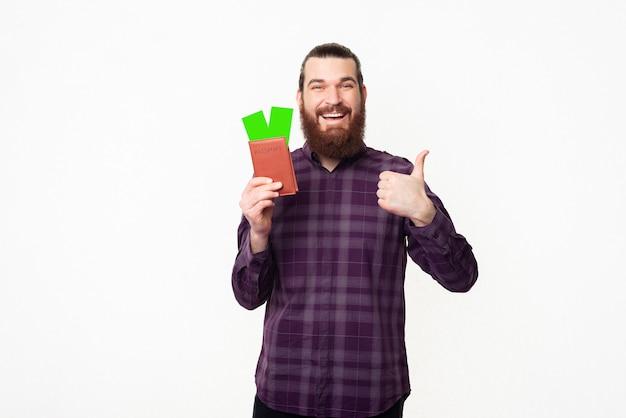 Jovem bonito barbudo alegre vestindo uma camisa xadrez mostrando o polegar para cima e o passaporte com os ingressos