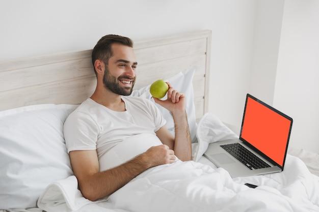 Jovem bonito barbudo calmo deitado na cama com lençol branco e cobertor no quarto em casa