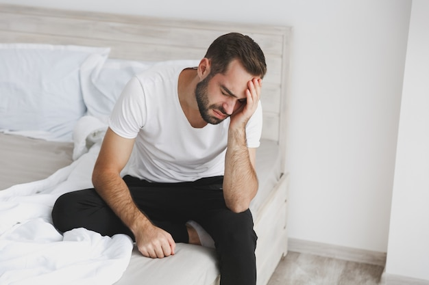 Jovem bonito barbudo calmo sentado na cama com lençol branco e cobertor no quarto em casa