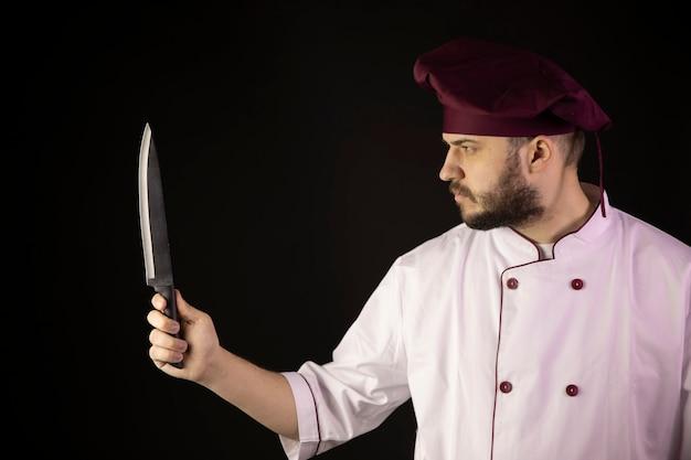 Jovem bonito barbudo chef homem de uniforme detém faca na mão olha atentamente