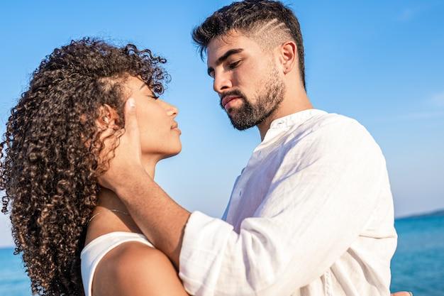 Jovem bonito barbudo com camisa branca agarra sua mulher hispânica encaracolada com força, segurando sua cabeça em suas mãos com uma expressão séria - visão de baixo ângulo em cores brilhantes e vivas