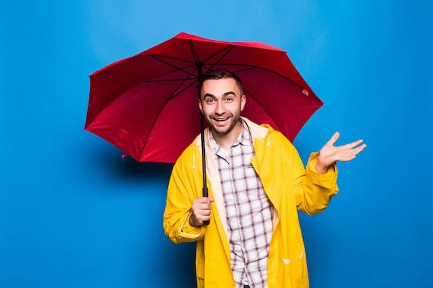 Jovem bonito barbudo com capa de chuva amarela e guarda-chuva vermelha tentando ver se está chovendo isolado sobre fundo azul