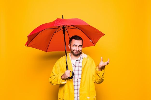 Jovem bonito barbudo com capa de chuva amarela e guarda-chuva vermelha tentando ver se está chovendo isolado sobre fundo laranja