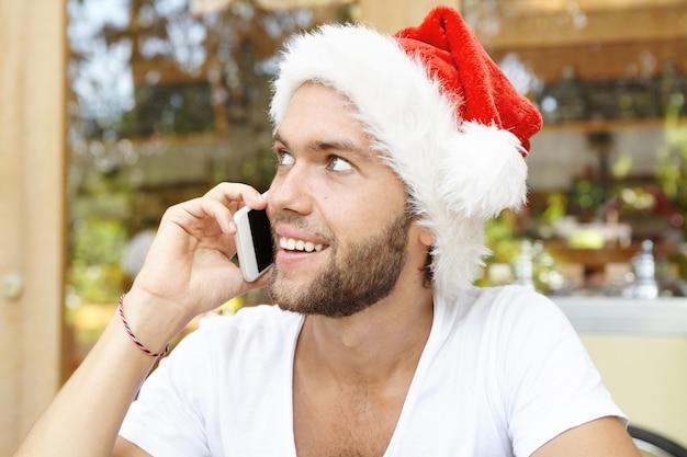 Jovem bonito barbudo com chapéu de papai noel e telefone celular genérico