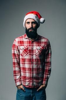 Jovem bonito barbudo com chapéu vermelho de natal na parede cinza