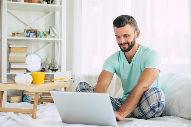 Jovem bonito barbudo com roupas casuais está trabalhando em casa enquanto está sentado na cama. cara confiante com um laptop e smartphone bebe café no quarto.